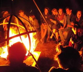 Jugendliche sitzen am Feuer: Kanufreizeit Polen