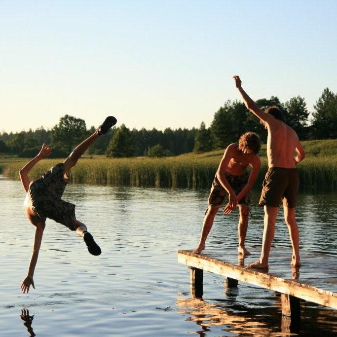 Jugendliche toben auf einem Steg am See: Kanufreizeit in Polen